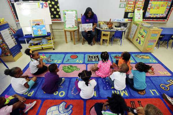 """Pre-k students listen as Kim Wycoff reads """"The Night Before Kindergarten"""" on Thursday morning. Conn's partnered with nonprofit group First Book to donate 1,000 books to the students of Anthony F. Lucas Pre-K Center on Thursday morning. Volunteers with the company read a book, """"The Night Before Kindergarten,"""" to the students before allowing them to pick two books apiece from a selection of titles in the library. Photo taken Thursday 5/14/15 Jake Daniels/The Enterprise"""