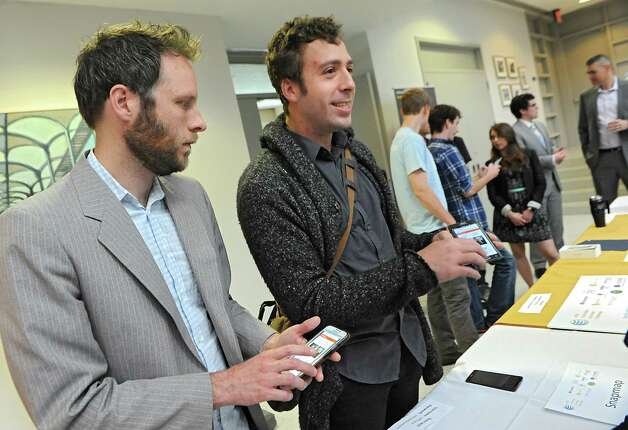 """Eric Krans of Altamont, left, and Alex Muro of Albany talk about their 2nd place winning app Electorate after AT&T announced the winners of its $18,000 """"app challenge"""" for local developers at the University at Albany on Thursday, May 14, 2015 in Albany, N.Y. The men received $5,000 for their second place app. (Lori Van Buren / Times Union) Photo: Lori Van Buren / 10031848A"""