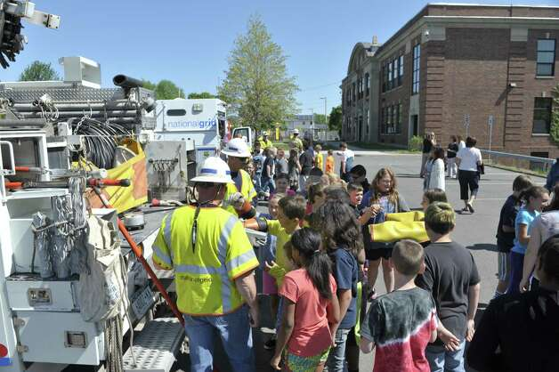 Students gather around National Grid line employees Bob Connors, foreground, and Richard Wood during a National Grid safety program outside of Van Schaick Grade School on Thursday, May 14, 2015, in Cohoes, N.Y. Fourth and fifth graders also got the chance to see how National Grid employees work while on the job.  (Paul Buckowski / Times Union) Photo: PAUL BUCKOWSKI / 10031847A