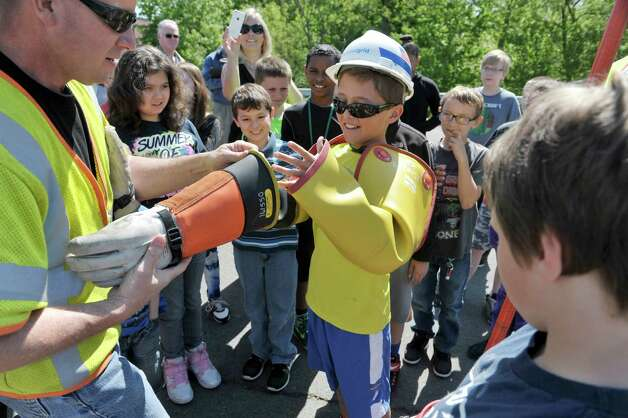 National Grid line employee Bob Connons, left, helps student John Sencer, 10, put on protective gear during a National Grid safety program outside of Van Schaick Grade School on Thursday, May 14, 2015, in Cohoes, N.Y. Fourth and fifth graders also got the chance to see how National Grid employees work while on the job.  (Paul Buckowski / Times Union) Photo: PAUL BUCKOWSKI / 10031847A