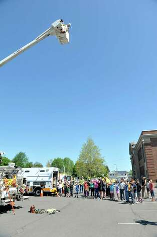 National Grid line employee Richard Wood, in bucket, looks down on students during a National Grid safety program outside of Van Schaick Grade School on Thursday, May 14, 2015, in Cohoes, N.Y. Fourth and fifth graders also got the chance to see how National Grid employees work while on the job.  (Paul Buckowski / Times Union) Photo: PAUL BUCKOWSKI / 10031847A