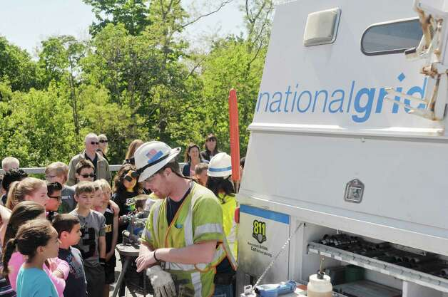 National Grid customer metering services employee Brian Nastke talks with students during a National Grid safety program outside of Van Schaick Grade School on Thursday, May 14, 2015, in Cohoes, N.Y. Fourth and fifth graders also got the chance to see how National Grid employees work while on the job.  (Paul Buckowski / Times Union) Photo: PAUL BUCKOWSKI / 10031847A
