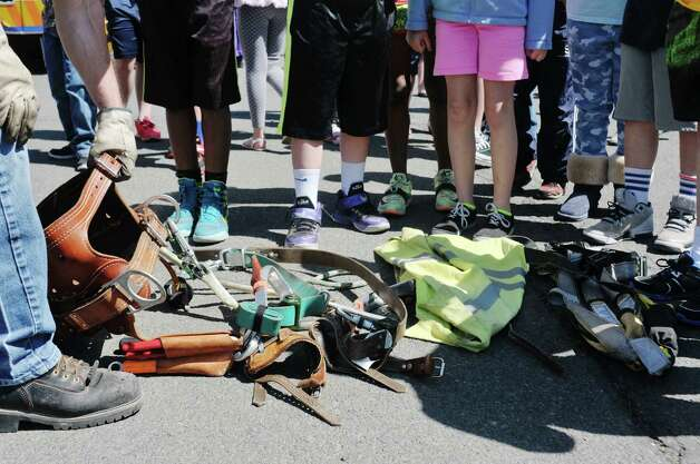 Students look over gear used by National Grid employees working out in the field during a National Grid safety program outside of Van Schaick Grade School on Thursday, May 14, 2015, in Cohoes, N.Y. Fourth and fifth graders also got the chance to see how National Grid employees work while on the job.  (Paul Buckowski / Times Union) Photo: PAUL BUCKOWSKI / 10031847A