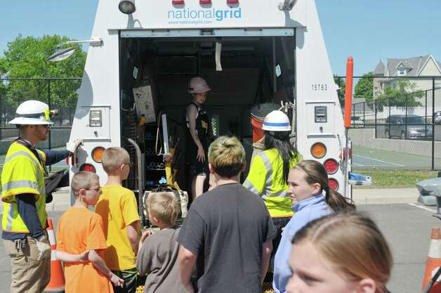 National Grid customer metering services employees, Don Clarke, background left, and Angela Fosmire, background right, give students a tour of their service truck during a National Grid safety program outside of Van Schaick Grade School on Thursday, May 14, 2015, in Cohoes, N.Y. Fourth and fifth graders also got the chance to see how National Grid employees work while on the job.  (Paul Buckowski / Times Union) Photo: PAUL BUCKOWSKI / 10031847A