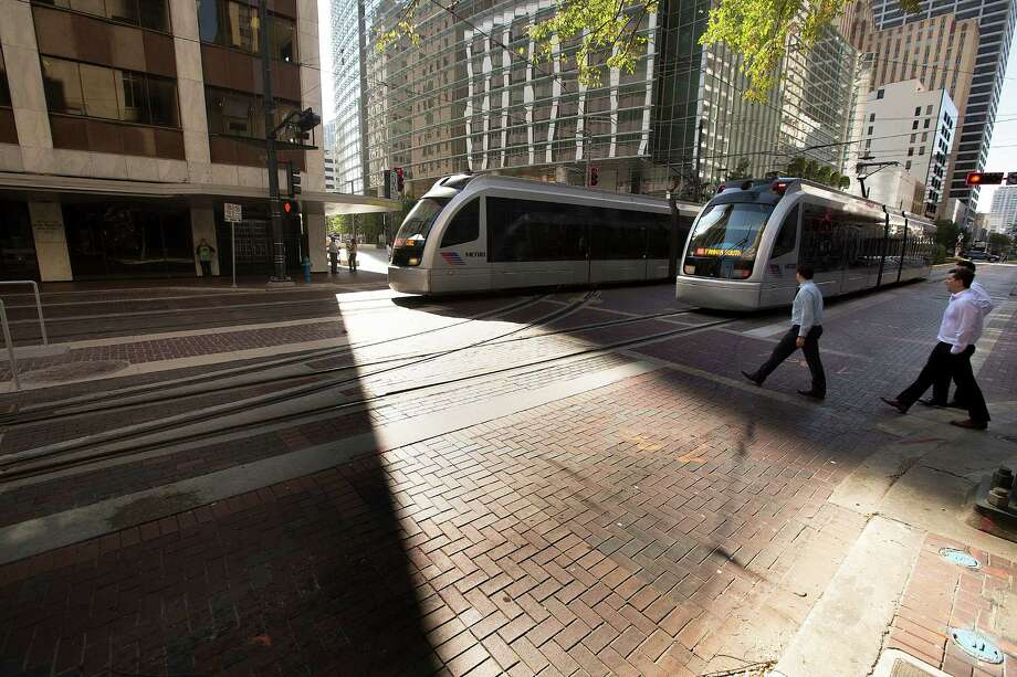 Metro Red Line trains make their way down Main Street at Capitol past the tracks for the Green and Purple Lines on Oct. 22, 2014. Photo: Johnny Hanson, Houston Chronicle / © 2014  Houston Chronicle