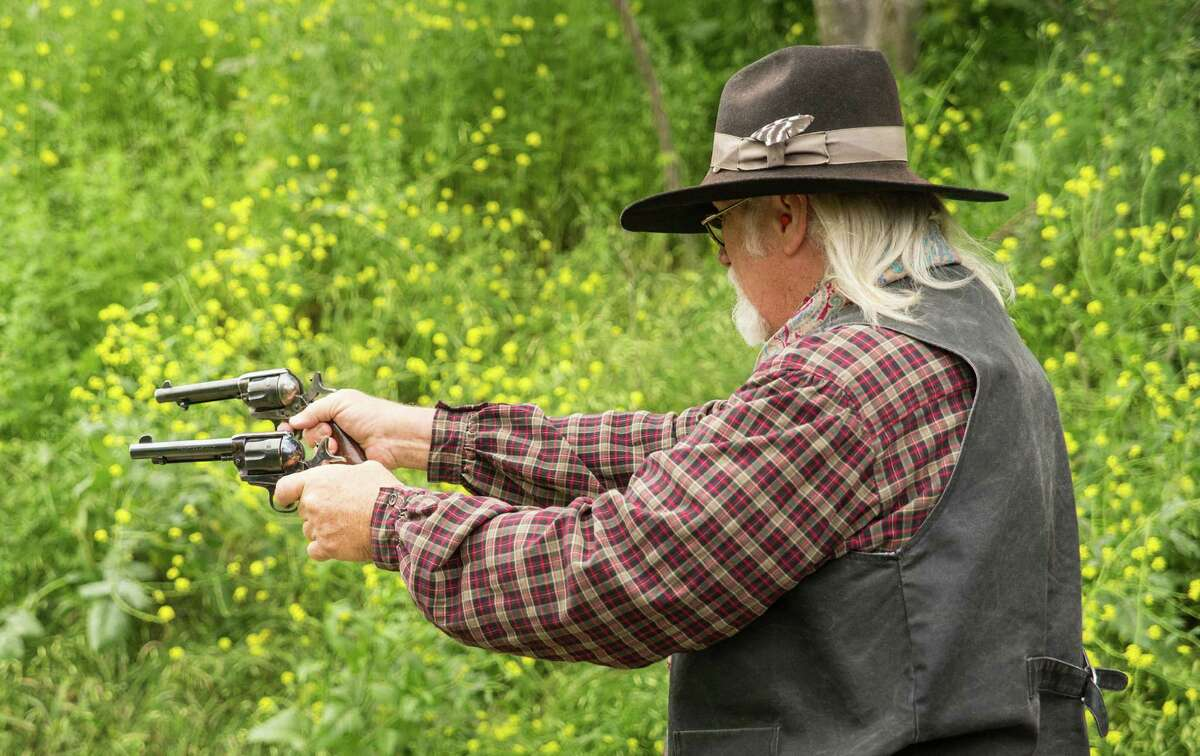 Mike Franklin, president of the South Texas Pistalaros, fires his pistols during a cowboy action shooting match at A Place to Shoot, a shooting range in San Antonio, on April 4, 2015.