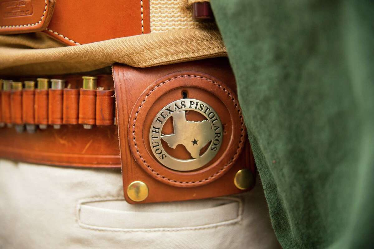 Members of the South Texas Pistolaros, a cowboy action shooting club, have badges proclaiming their membership as part of their costumes. The group practices cowboy action shooting at A Place to Shoot in San Antonio.