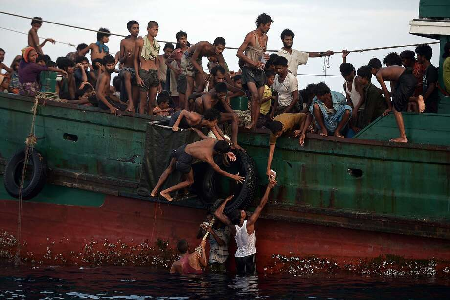 Rohingya migrants pass food supplies dropped by a Thai army helicopter to others aboard a boat drifting in Thai waters off the southern island of Koh Lipe in the Andaman sea on May 14, 2015.  A boat crammed with scores of Rohingya migrants -- including many young children -- was found drifting in Thai waters on May 14, with passengers saying several people had died over the last few days. Photo: Christophe Archambault, AFP / Getty Images