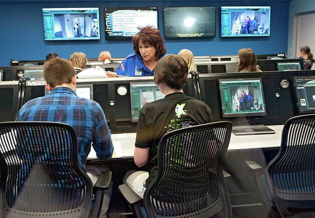 Commander Marie Dicristofaro talks to Tech Valley seniors Noah Hellman, 18, of Averill Park, left, and Grace Bombard, 17, from Schodack Landing in the mission control room at the Museum of Innovation and Science on Thursday, May 14, 2015 in Schenectady, N.Y. The new Challenger Learning Center opened in the museum today. (Lori Van Buren / Times Union) Photo: Lori Van Buren / 00031850A