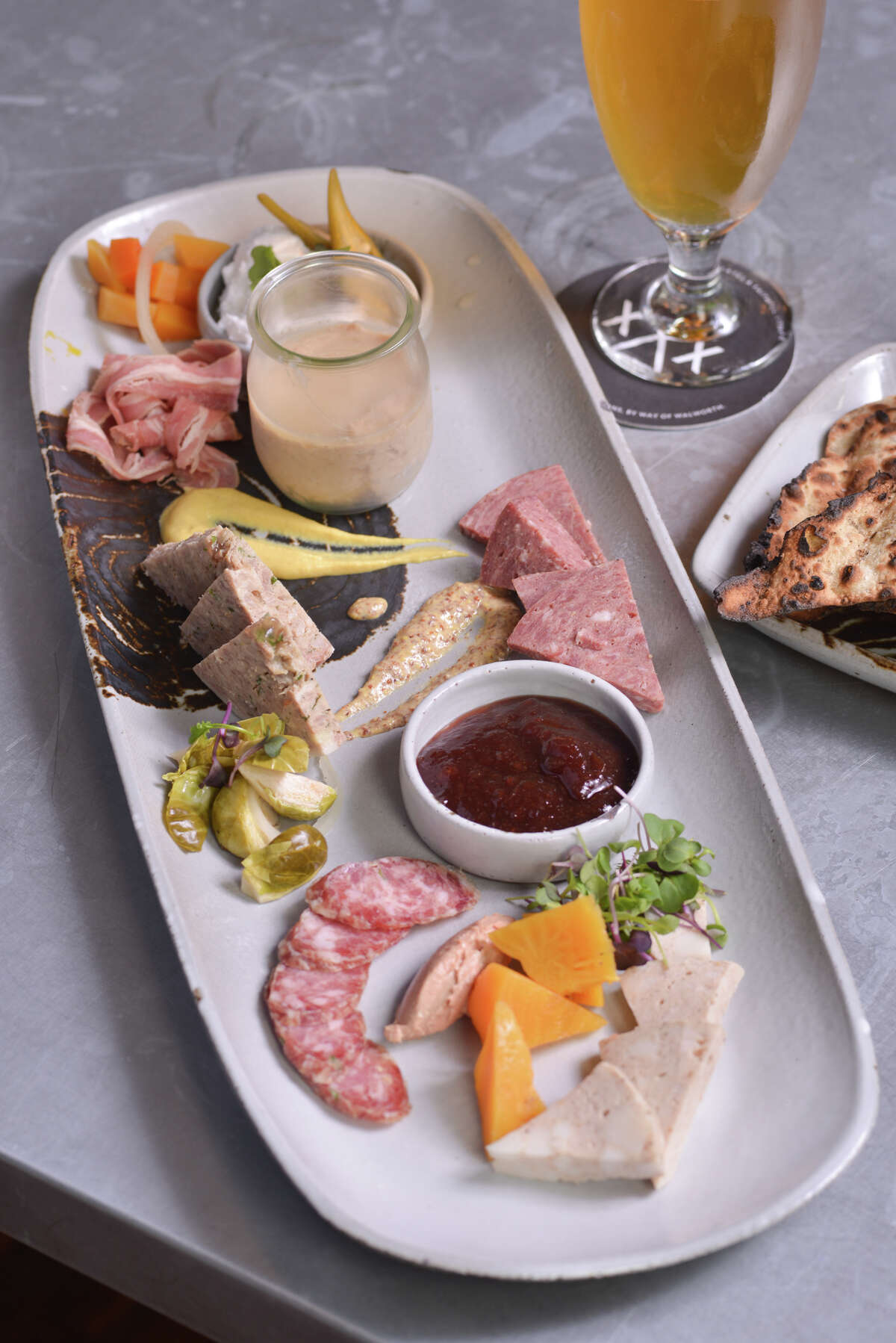 A charcuterie plate from Cured featuring mortadella, chicken liver mousse, jalapeño sauce, apple red wine jam, pickled Brussels sprouts, country style pork pate', smoked veal wurst, smoked lamb belly, and whipped pork butter and beer flatbread.