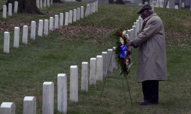 Herman Johnson, from Kansas City Missouri, adjusts a wreath at his father's grave, Henry Johnson, at Arlington National Cemetery in Washington D.C., Thursday afternoon, January 10, 2002.  Herman Johnson saw his father's grave for the first time on Thursday during a wreath laying ceremony attended by New York State Governor George Pataki.  It was not known until very recently where the WWI  hero Henry Johnson was buried.  Henry Johnson was  a member of the 369th Regiment, a New York National Gaurd outfit. (Times Union/Paul Buckowski) Photo: PAUL BUCKOWSKI / ALBANY TIMES UNION