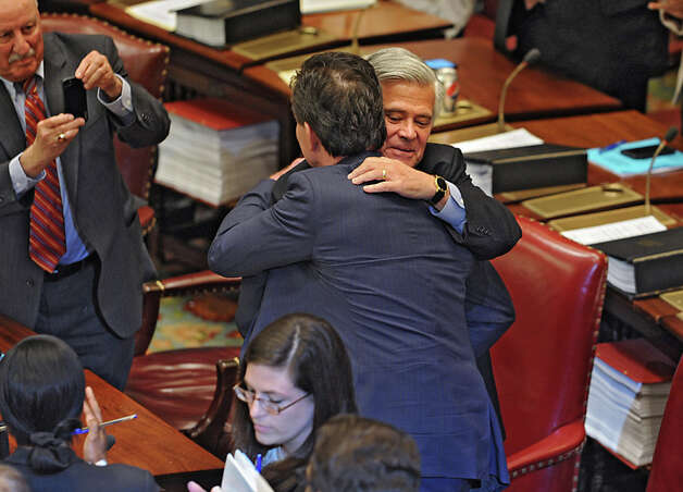 Senator Dean Skelos congratulates Senator John Flanagan, right, after Flanagan received the oath of office to be the new Senate Majority Leader in the Senate Chamber at the Capitol on Monday, May 11, 2015 in Albany, N.Y. Senator Kenneth LaValle, left, takes a photo with his phone. (Lori Van Buren / Times Union) Photo: Lori Van Buren, Albany Times Union