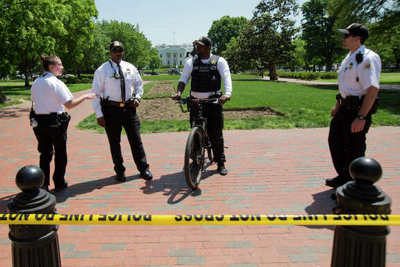 Uniformed Secret Service police officers stand watch at Lafayette Park not far from the White House and near where a man was illegally flying a small drone.