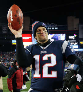 New England Patriots quarterback Tom Brady holds up the game ball after an NFL divisional playoff football game against the Baltimore Ravens in in January.