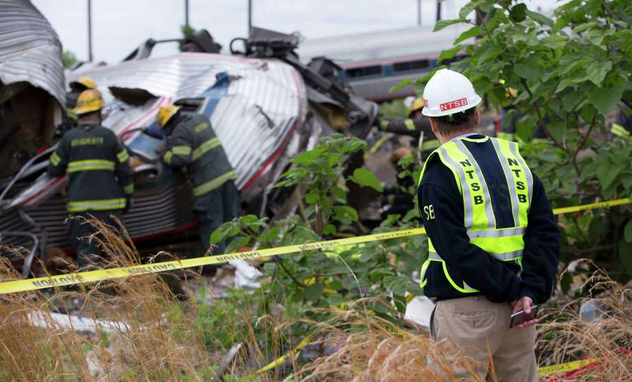 In this handout image supplied by NTSB, NTSB member Robert Sumwalt works on the scene of the Amtrak Train derailment on Wednesday May 13, 2015 in Philadelphia, Pennsylvania. Service has been interrupted after Amtrak train derailed in Philadelphia Tuesday, killing at least eight people and injured more than 200. Photo: Contributed Photo, NTSB/Contributed Photo / Connecticut Post Contributed