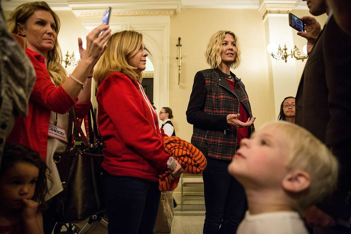 Actor Jenna Elfman, right, speaks to a reporter in opposition of SB 277, an effort to close California's vaccine loophole, at the State Capitol in Sacramento, California, May 14, 2015. The bill passed the senate Thursday and now moves onto the assembly. Elfman is opposed to SB277, but favors vaccinations.