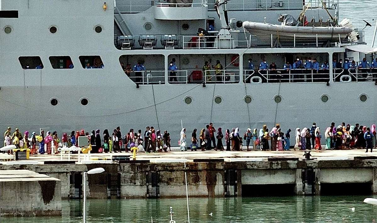 Rohingya women migrants and children stand in a queue to board a Malaysian Navy ship at the naval base in Langkawi on May 14, 2015 to be transferred to a mainland immigration depot. Malaysia has turned away two vessels carrying a combined 600 migrants, according to an official who spoke on condition of anonymity on May 14, as concern mounted in the region over the fate of boatloads of people stranded at sea.