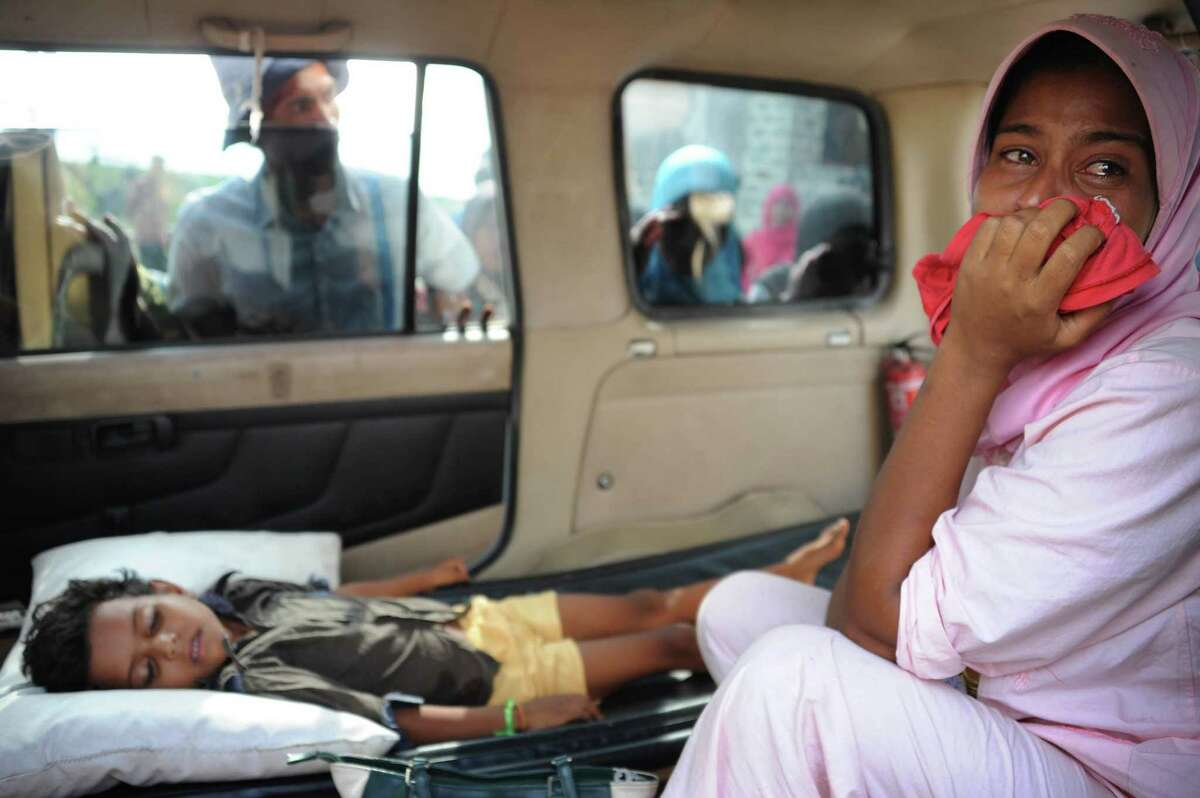 """A migrant Rohingya woman (R) from Myanmar cries as she waits for an ambulance to evacuate her sick child from the Kuala Cangkoi relocation area in Aceh province to a hospital on May 14, 2015 where nearly 600 migrants mostly Rohingyas from Myanmar and Bangladesh were relocated by Indonesian authorities. Meanwhile, Malaysia turned away two vessels carrying hundreds of migrants while one boat turned up on May 14 in Thai waters, as critics accused Southeast Asian governments of playing a game of """"human ping pong"""" with the lives of desperate boatpeople. Malaysia had already said this week it would turn away boats bearing desperate migrants from Myanmar and Bangladesh unless they are in imminent danger of sinking, following in the footsteps of neighbouring Indonesia."""