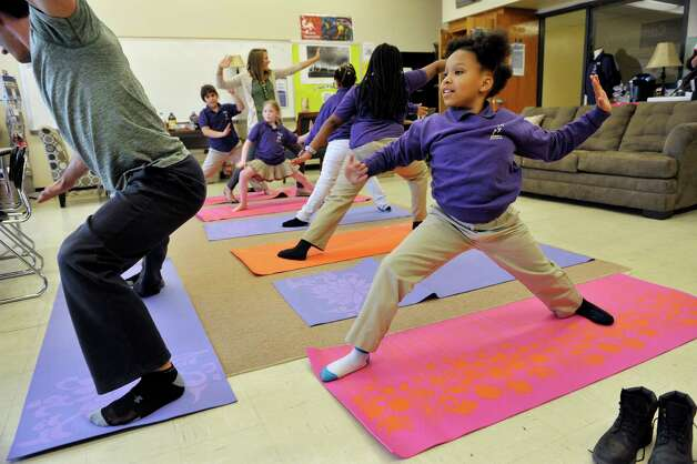 Fourth grader Nyla Lockett, 9, follows along as instructor Shawn Huber, right, with Freestyle Fitness and Yoga, shows children moves in Budokon during a Project Based Learning program at Troy School 2 on Wednesday, May 13, 2015, in Troy, N.Y.  The program is a 6-week program that meets on Wednesday afternoons for Grades three through five.   (Paul Buckowski / Times Union) Photo: PAUL BUCKOWSKI / 00031786A