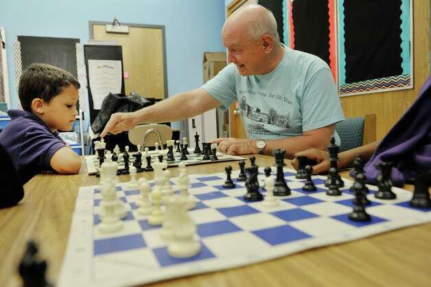 Fourth grader, Jaiden Rodriguez, left, learns chess from John McManus with The Right Move during a Project Based Learning program at Troy School 2 on Wednesday, May 13, 2015, in Troy, N.Y.  The program is a 6-week program that meets on Wednesday afternoons for Grades three through five.   (Paul Buckowski / Times Union) Photo: PAUL BUCKOWSKI / 00031786A