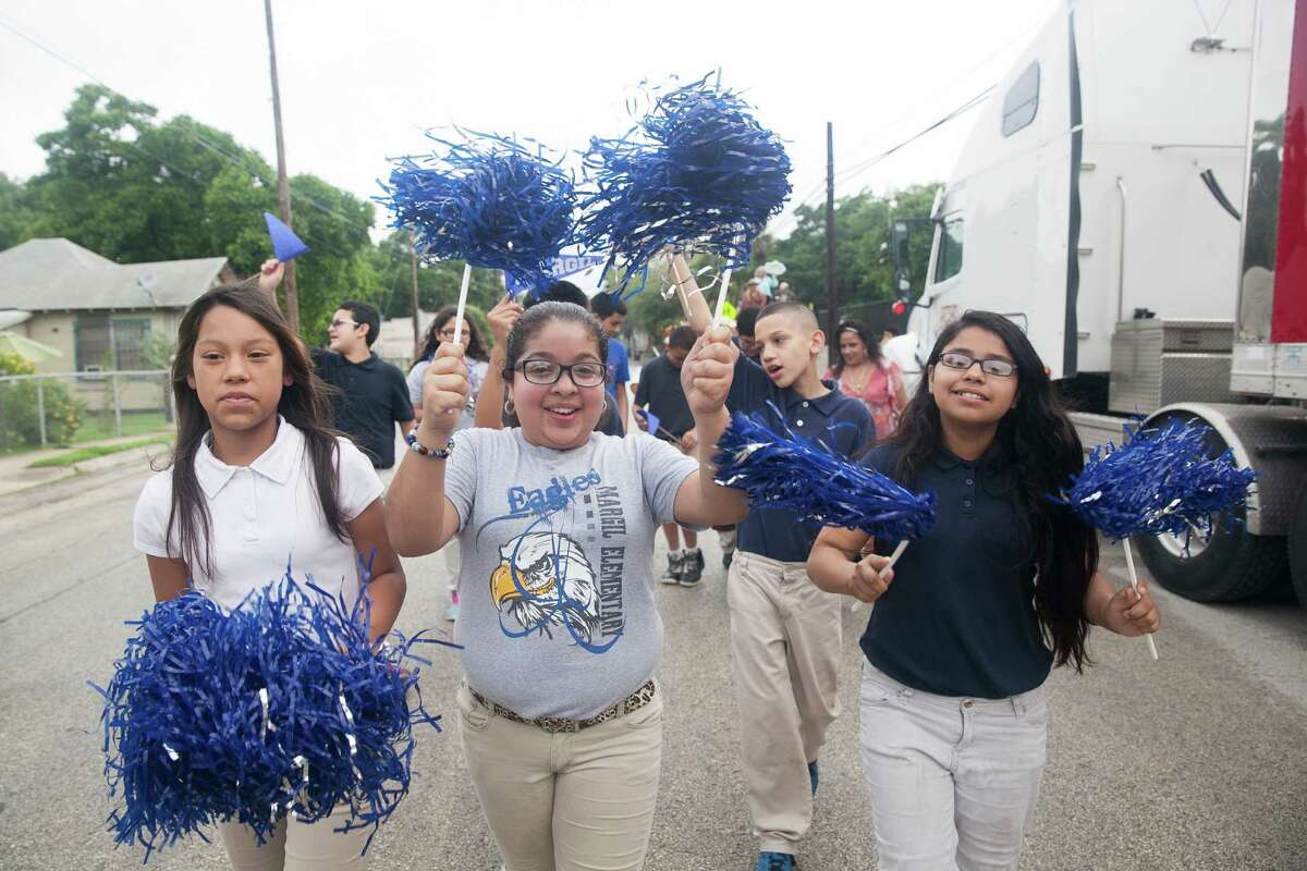 Fifth-graders Serenity Chacon (from left), Desiree Montes, and Jade Aguero from Margil Elementary School lead a procession Thursday at LiftFund.