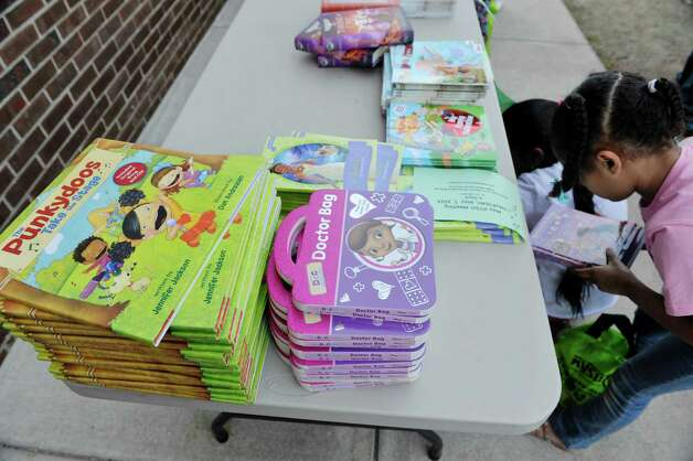 Children look over books during a book giveaway at  Central Park International Magnet School on Thursday, May 14, 2015, in Schenectady, N.Y.  The book program is a partnership between First Book, the American Federation of Teachers (AFT), and New York State United Teachers (NYSUT) and Schenectady Federation of Teachers.  Each child was allowed to pick out two books during the event.  500,000 free books are being given out to children in the area through the program.  (Paul Buckowski / Times Union) Photo: PAUL BUCKOWSKI / 00031825A