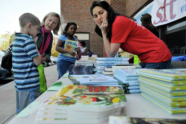 Cesaera Pirrone, right, a seventh and eighth grade social studies teacher helps a student find a book  during a book giveaway at  Central Park International Magnet School on Thursday, May 14, 2015, in Schenectady, N.Y.  The book program is a partnership between First Book, the American Federation of Teachers (AFT), and New York State United Teachers (NYSUT) and Schenectady Federation of Teachers.  Each child was allowed to pick out two books during the event.  500,000 free books are being given out to children in the area through the program.  (Paul Buckowski / Times Union) Photo: PAUL BUCKOWSKI / 00031825A