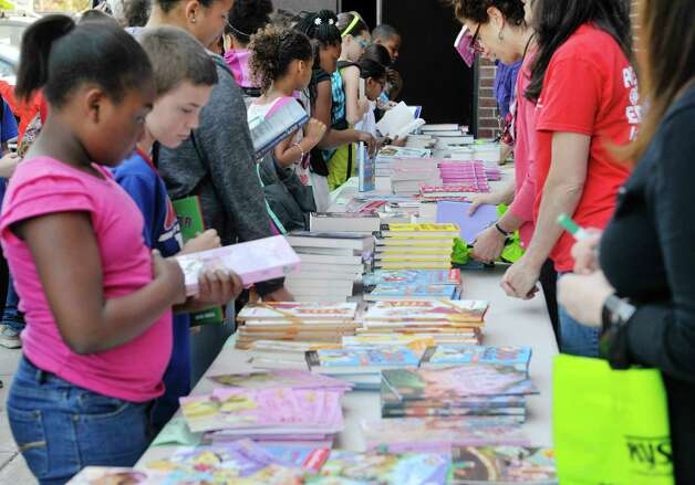 Children pick out books during a book giveaway at  Central Park International Magnet School on Thursday, May 14, 2015, in Schenectady, N.Y.  The book program is a partnership between First Book, the American Federation of Teachers (AFT), and New York State United Teachers (NYSUT) and Schenectady Federation of Teachers.  Each child was allowed to pick out two books during the event.  500,000 free books are being given out to children in the area through the program.  (Paul Buckowski / Times Union) Photo: PAUL BUCKOWSKI / 00031825A