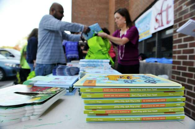 Parents pick out books for their children during a book giveaway at  Central Park International Magnet School on Thursday, May 14, 2015, in Schenectady, N.Y.  The book program is a partnership between First Book, the American Federation of Teachers (AFT), and New York State United Teachers (NYSUT) and Schenectady Federation of Teachers.  Each child was allowed to pick out two books during the event.  500,000 free books are being given out to children in the area through the program.  (Paul Buckowski / Times Union) Photo: PAUL BUCKOWSKI / 00031825A