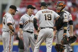 San Francisco Giants starting pitcher Tim Lincecum, second from left, meets with pitching coach Dave Righetti (19) and teammates on the mound in the first inning of a baseball game against the Cincinnati Reds, Thursday, May 14, 2015, in Cincinnati. (AP Photo/John Minchillo)