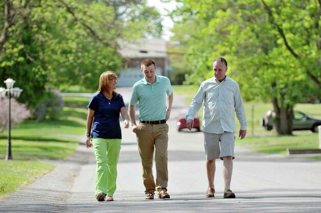 Liz Bennison, left, and her husband Pat Bennison, right, walk with their son Dan Bennison outside their home on Monday, May 11, 2015, in Albany, N.Y.   (Paul Buckowski / Times Union) Photo: PAUL BUCKOWSKI / 00031784A