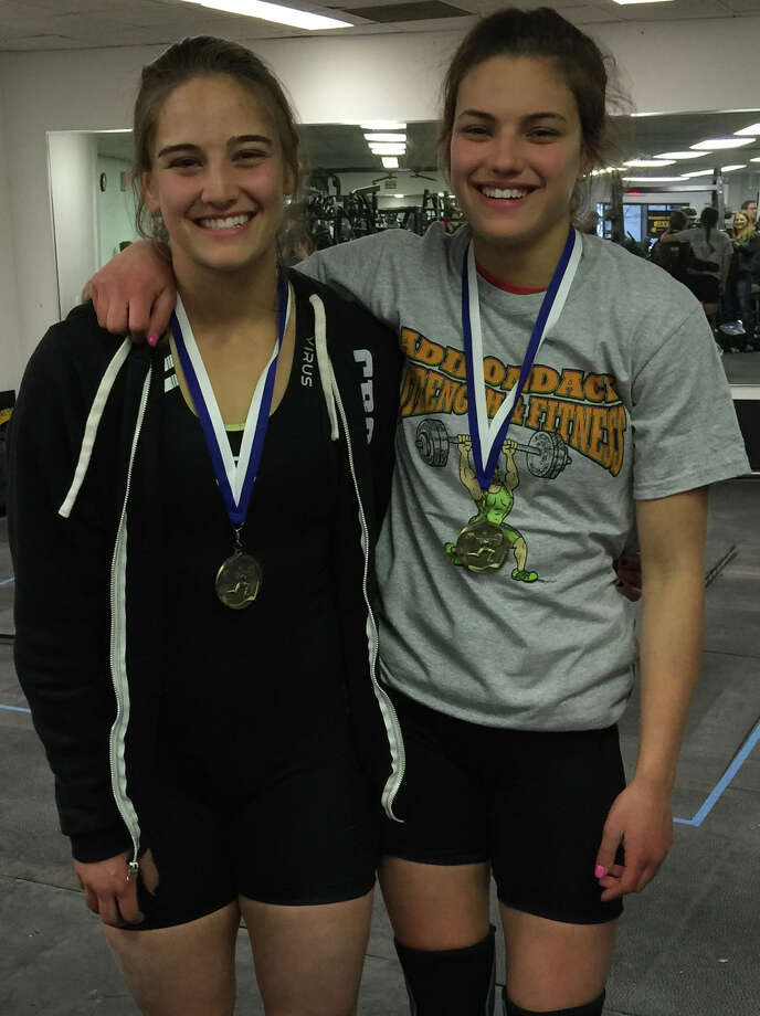 : Newtown High's Celia, left, and Romy Gold show off gold medals they recently won a weightlifting competition. The sisters have qualified to compete in the 2015 CrossFit Games in Carson, Calif. in July. Celia, a junior and Romy, a freshman, are both starters for the Newtown High girls lacrosse team. Photo: Contributed Photo / Stamford Advocate Contributed