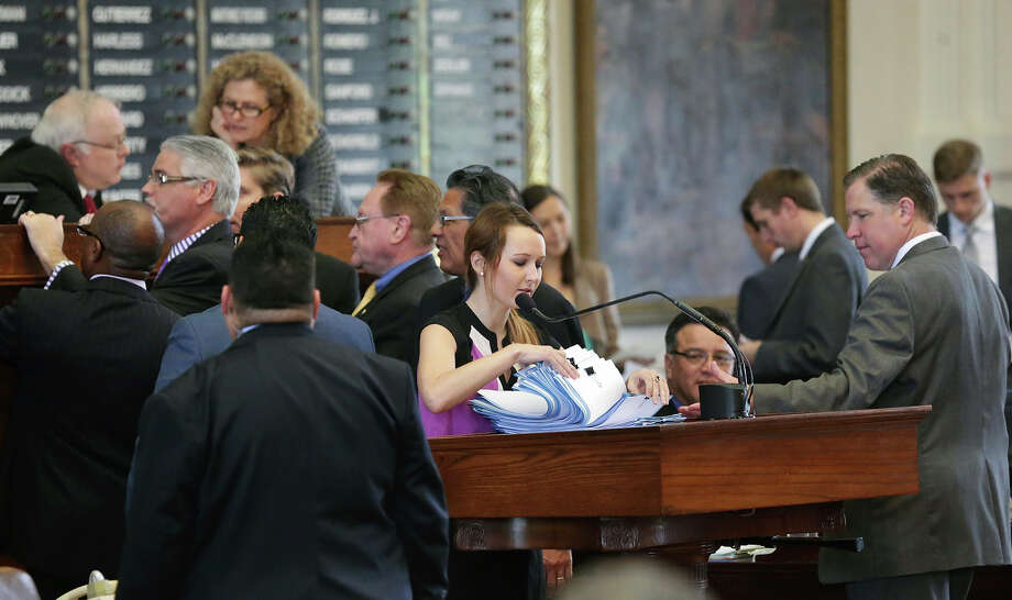 With a frenzy of lawmakers moving around her, Reading Clerk  Elizabeth Milam goes through a pile of bills before the body while the  House of Representatives and the Senate  governing bodies work on last minute legislation in Austin on May 14, 2015. Photo: Tom Reel, San Antonio Express-News