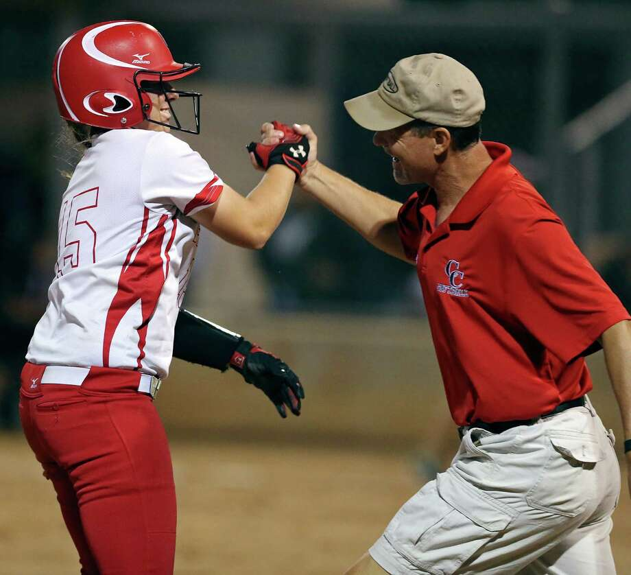 New Braunfels Canyon's Sydney Owens celebrates with head coach Kevin Randle after hitting the go-ahead two-run triple in the bottom of the sixth inning against Southwest during Game 1 of the Class 6A best-of-3 third-round high school softball playoff series Thursday May 14, 2015 at North East ISD's West Field. New Braunfels Canyon won 3-1. Photo: Edward A. Ornelas, Staff / San Antonio Express-News / © 2015 San Antonio Express-News
