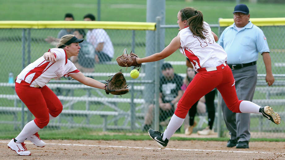 New Braunfels Canyon's Nicole Flitton (right) misses a pop-up hit as teammate Sydney Owens moves in on the play during Game 1 of the Class 6A best-of-3 third-round high school softball playoff series Thursday May 14, 2015 at North East ISD's West Field. Aguilar was safe at first. New Braunfels Canyon won 3-1. Photo: Edward A. Ornelas /San Antonio Express-News / © 2015 San Antonio Express-News