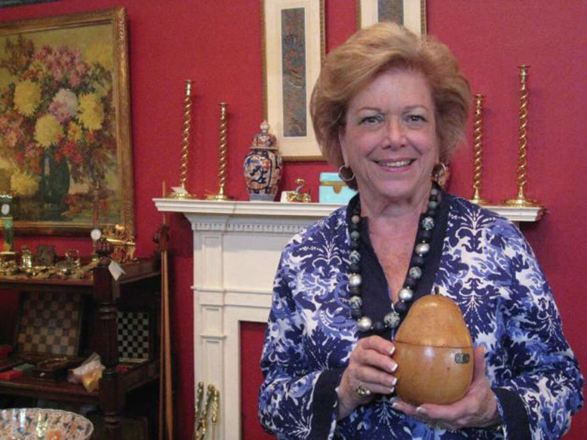 Sally B. Kaltman, owner of Sallea Antiques on Elm Street in New Canaan, stands in her shop holding an English pear-shaped tea caddie made of polished fruitwood circa 1780 to 1800. Kaltman has announced that her store, Sallea Antiques, will be closing in August, and a liquidation sale began on May 14.