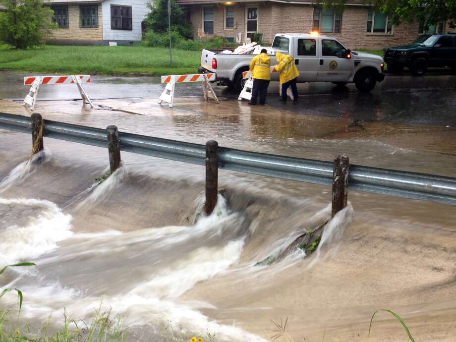 Public works employees of the city of San Antonio set up roadblocks at Danville and Overbrook in Balcones Heights where water has covered the road, on Friday, May 15, 2015. Photo: Bob Owen/Express News
