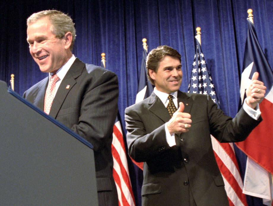 Texas Governor Rick Perry gives his gubernatorial re-election supporters a double thumbs up as President George W. Bush takes the podium to fully support his former lt. governor in Houston Friday evening, June 14, 2002. Photo: Kevin Fujii, Houston Chronicle / Houston Chronicle