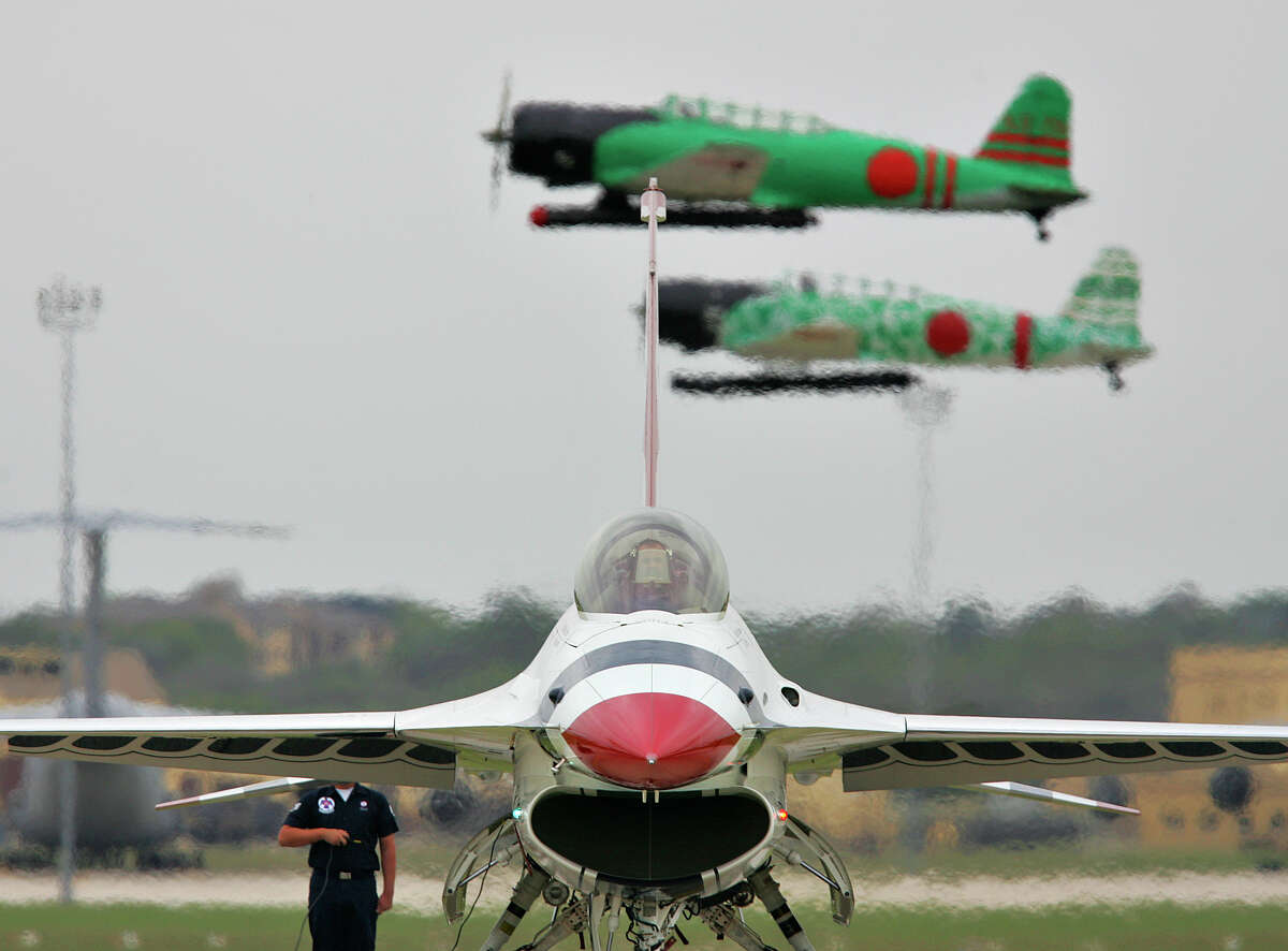 The Air Force Thunderbirds perform an engine run during 2006 Lackland Airfest. Replica Japanese aircraft fly behind them.