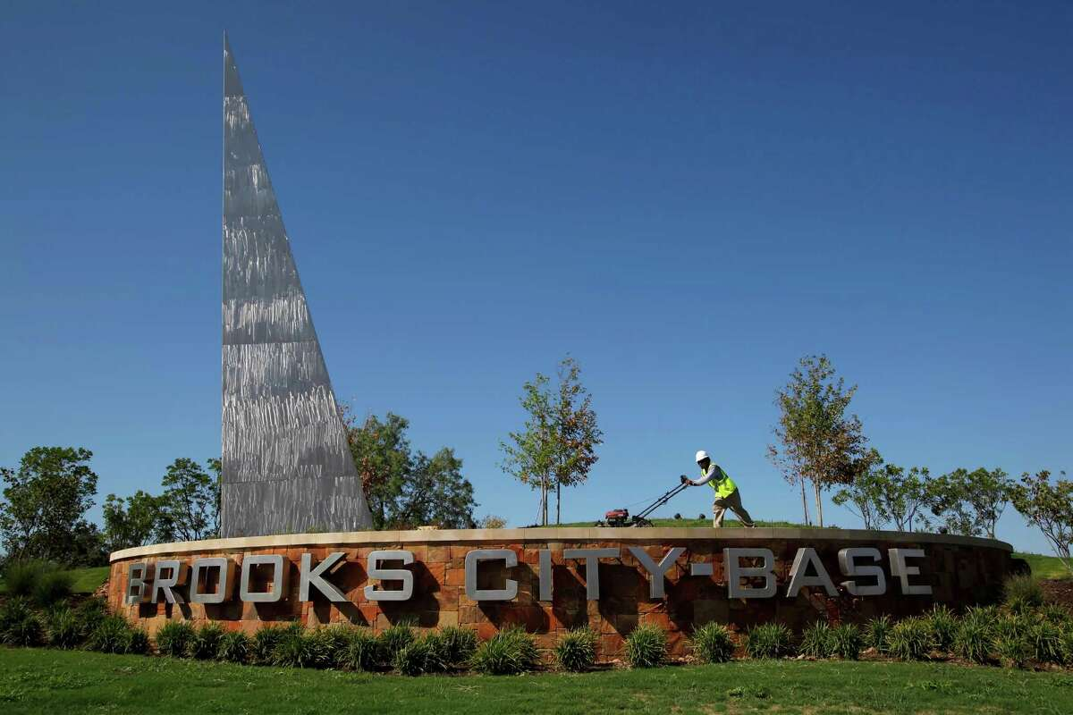 A worker mows the grass Wednesday Aug. 24, 2011 at the main entrance to Brooks City-Base on San Antonio's South Side.