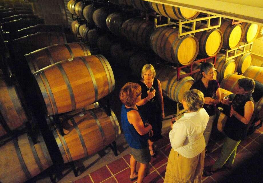 Tasters enjoy comparing wines via a barrel tasting during a tour at Grape Creek Vineyards on U.S. 290. Photo: Courtesy Grape Creek Vineyards