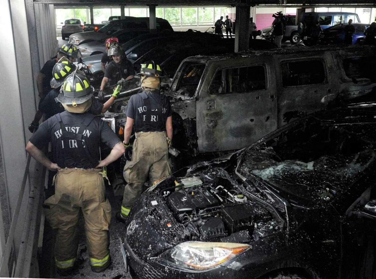Firefighters work to extinguish a three-car fire in a parking garage located at the intersection of Elgin Street and Milam Street Friday, May 15, 2015, in Houston.