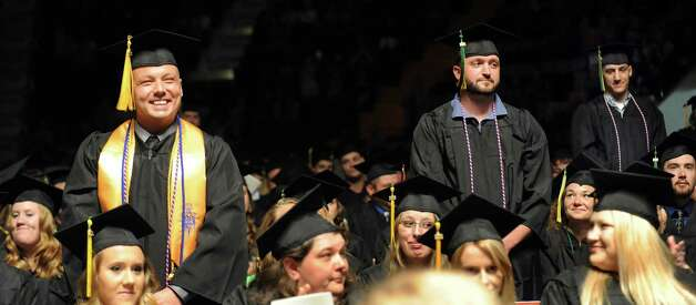 Graduates who have served in the military stands as they are recognized  during commencement exercises on Thursday, May 14, 2015, at Glens Falls Civic Center in Glens Falls, N.Y. (Cindy Schultz / Times Union) Photo: Cindy Schultz, Albany Times Union / 00031515A