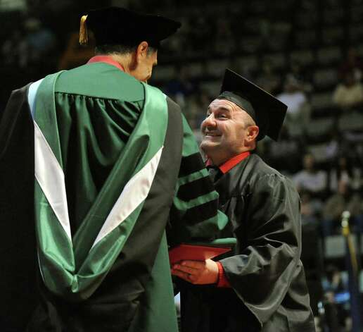 SUNY Plattsburgh graduate James Blair, right, receives his diploma during commencement exercises on Thursday, May 14, 2015, at Glens Falls Civic Center in Glens Falls, N.Y. (Cindy Schultz / Times Union) Photo: Cindy Schultz, Albany Times Union / 00031515A
