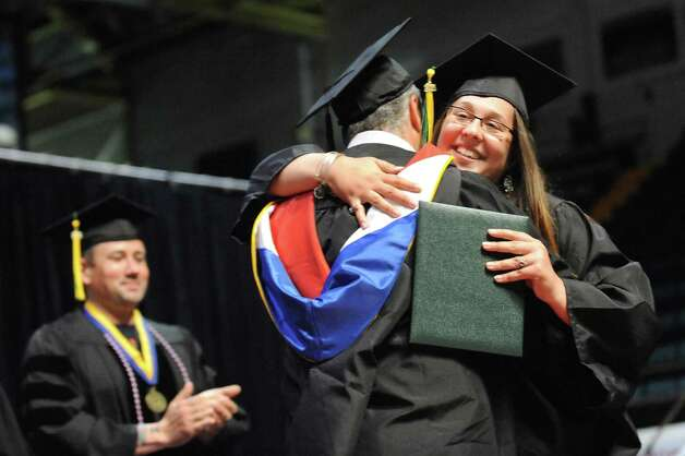 SUNY Adirondack graduate Danielle Dennett, right, embraces her father, Prof. Daniel Dennett, center, when he delivers her diploma during commencement exercises on Thursday, May 14, 2015, at Glens Falls Civic Center in Glens Falls, N.Y. (Cindy Schultz / Times Union) Photo: Cindy Schultz, Albany Times Union / 00031515A