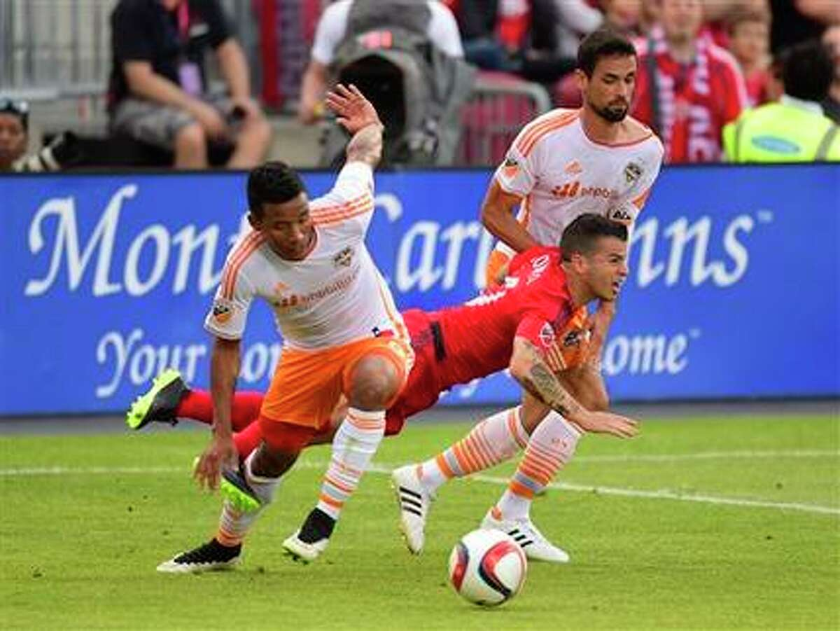 El hondureño Luis Garrido, y el español Raúl Rodríquez, despojan del balón a Sebastián Goncalves en el triunfo 2-1 del Dynamo sobre Toronto en Canadá.