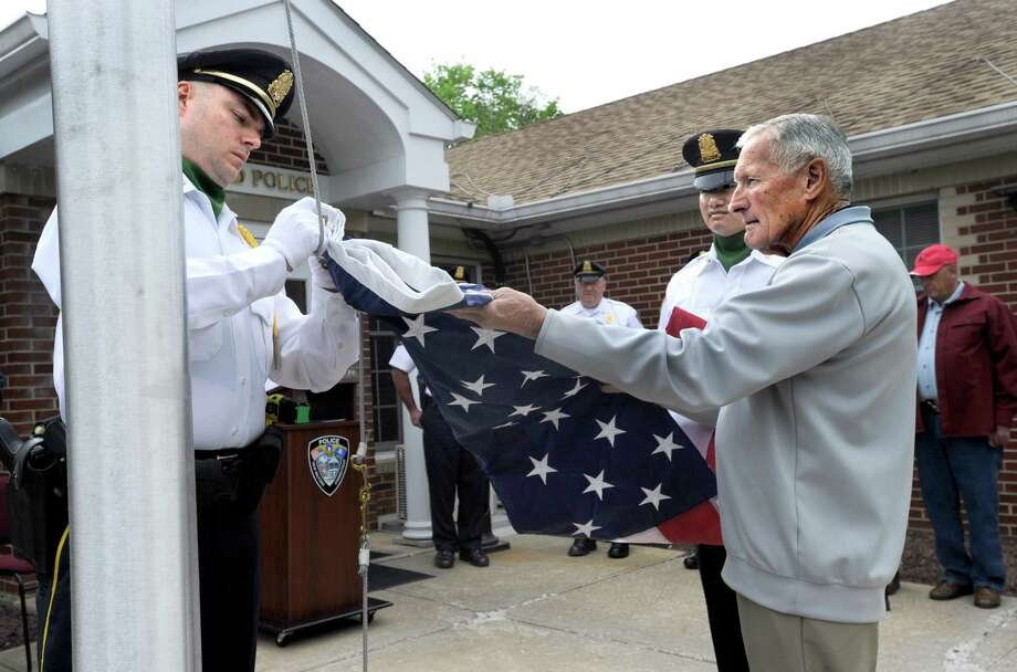 Sgt. Ed Hannan, left, and Officer Dru Sin, part of an Honor Guard, and Larry Couch, a nephew,   unfold and hook an American flag to raise on a new flag poll that is part of the memorial to the late New Milford Police Office H. Kenneth Couch. New Milford Police Officer H. Kenneth Couch who died during a water rescue in the Housatonic River on June 3, 1964, is remembered with a memorial monument and plaque during a ceremony at the New Milford Police Station Friday, May 15, 2015. Photo: Carol Kaliff / The News-Times