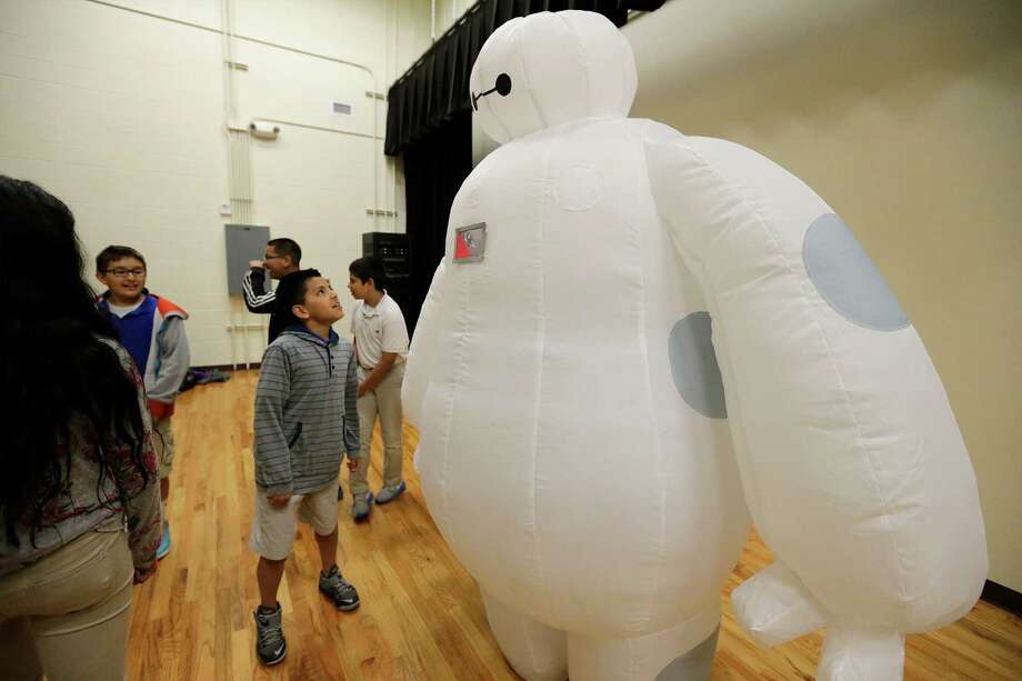 Fifth-grade student Samuel Beltran looks up at Big Hero 6 protagonist Baymax, as worn by Sarah Allen, after a school rally at SAISD's Mission Academy. Allen and other members of Cos 4 A Cause joined the  rally to award students for good character. Photo: Kin Man Hui /San Antonio Express-News / ©2015 San Antonio Express-News