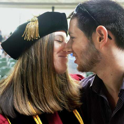 Graduate Courtney Alpert, left, of Boston gets a kiss from boyfriend Josh Finkelstein of Long Island before the start of Albany Law School Commencement Ceremonies at Saratoga Performing Arts Center Friday May 15, 2015 in Saratoga Springs, NY.  (John Carl D'Annibale / Times Union) Photo: John Carl D'Annibale / 00031496A