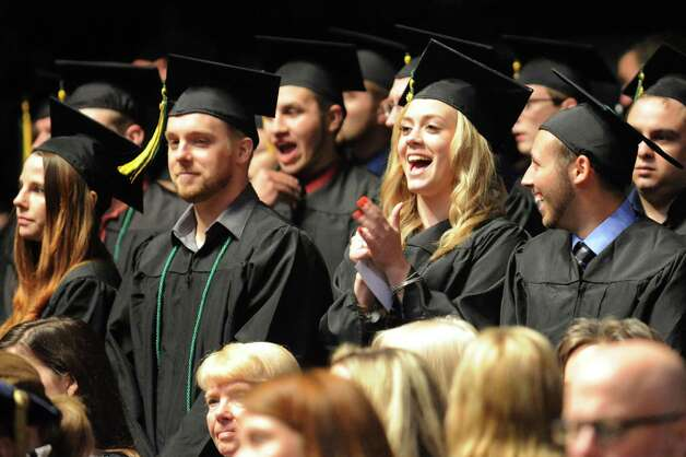 SUNY Adirondack graduates stand to receive their diplomas during commencement exercises on Thursday, May 14, 2015, at Glens Falls Civic Center in Glens Falls, N.Y. (Cindy Schultz / Times Union) Photo: Cindy Schultz / 00031515A